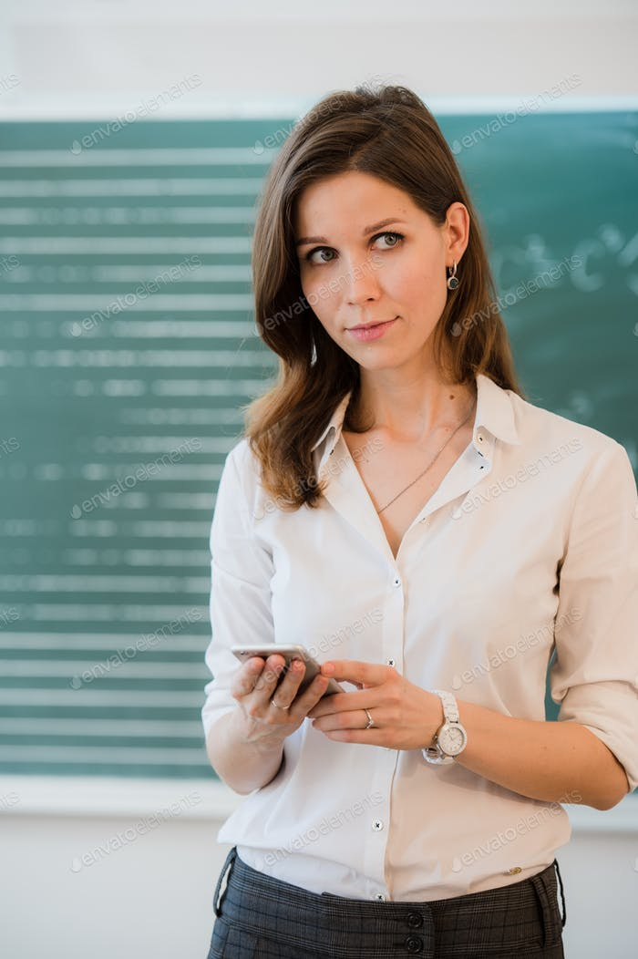 Female teacher or student with a phone at classroom in front of chalkboard