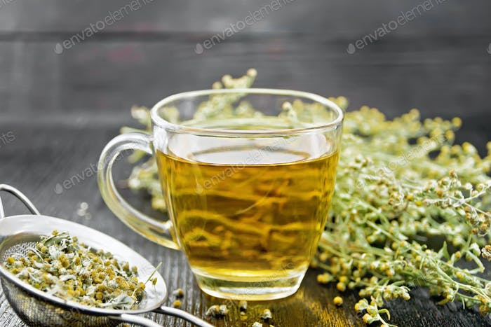 Tea of gray wormwood in glass cup with strainer on board