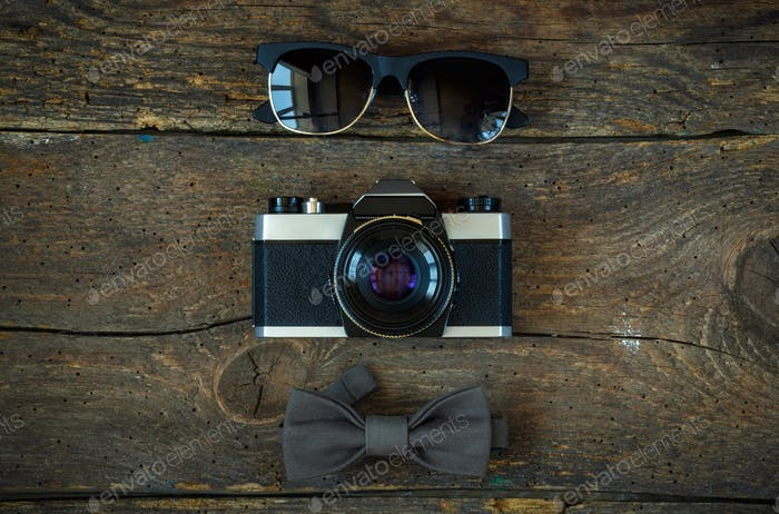 Sunglasses, old-fashioned camera and bow tie