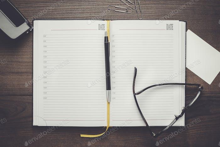persönlicher Organizer und Stift mit Brille auf dem Tisch