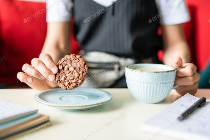 Businesswoman holding round chocolate cookie with nuts over plate