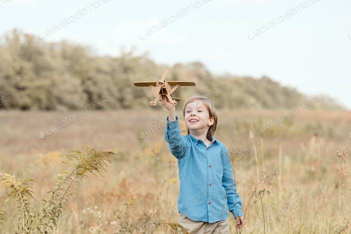 glückliches kleines Kind auf dem Feld spielt mit Spielzeugflugzeug auf dem Feld