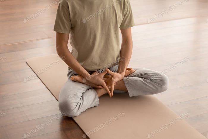 Low section of young man sitting on mat and keeping hands between crossed legs
