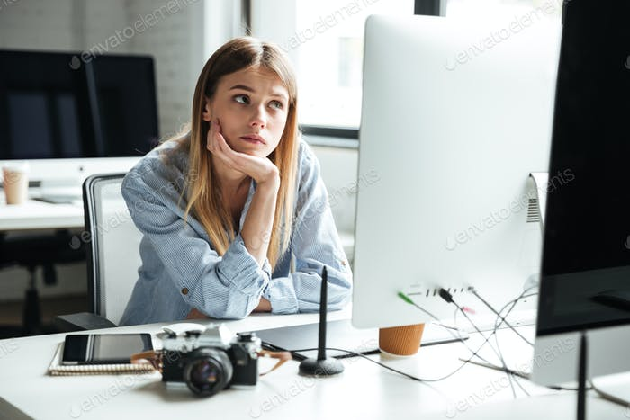 Serious young woman work in office using computer