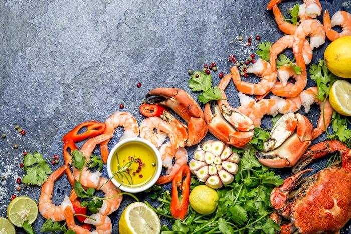Frische rohe Meeresfrüchte - Garnelen und Krabben mit Kräutern und Gewürzen auf dunkelgrauem Hintergrund