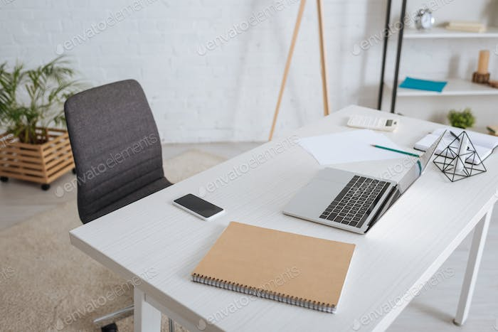 laptop near smartphone with blank screen on white table