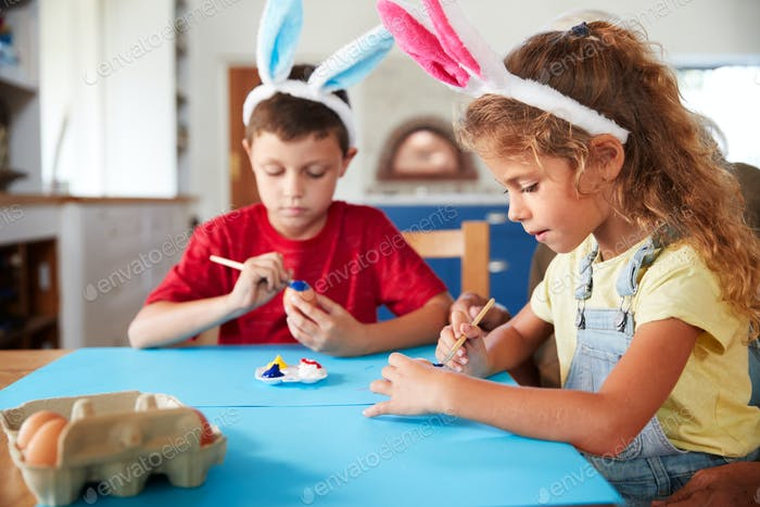 Children Wearing Rabbit Ears Decorating Easter Eggs At Home Together