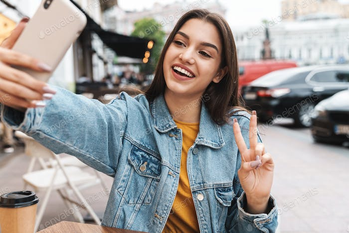 Image of woman taking selfie on cellphone and gesturing peace sign