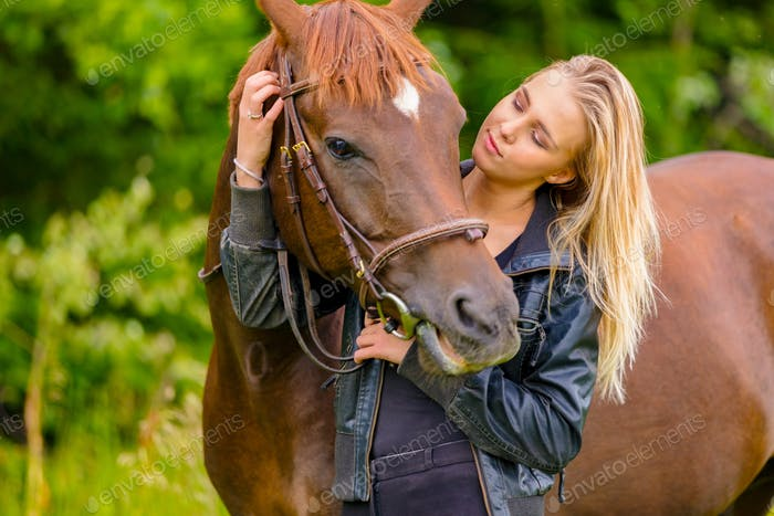 Beautiful woman communicate with her arabian horse in the field