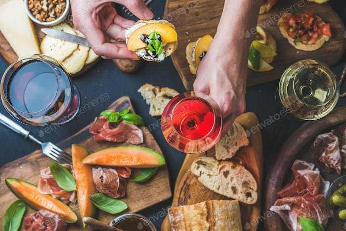 Italian wine snack variety, man's hands holding glass of rose