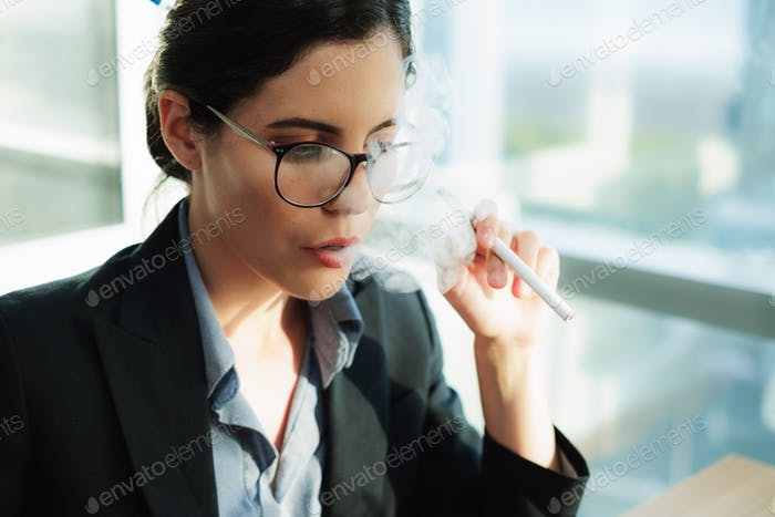 Stressed female executive vaping at work while using laptop Copyspace