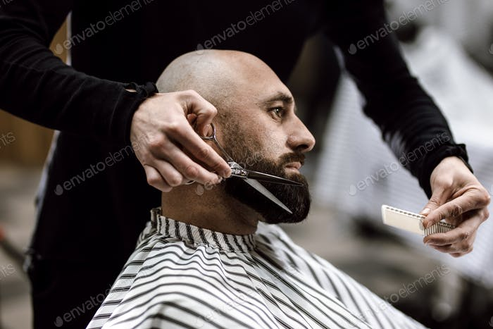 Fashion barber dressed in a black clothes scissors beard of brutal man in the stylish barbershop