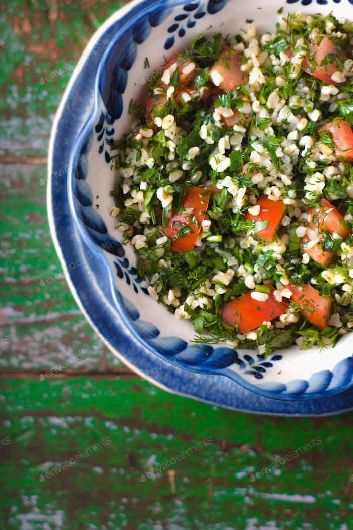 Tabouli middle eastern salad at glass bowl over floral napkin