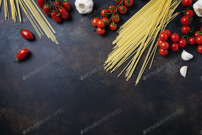 spaghetti, tomato and garlic on the black table