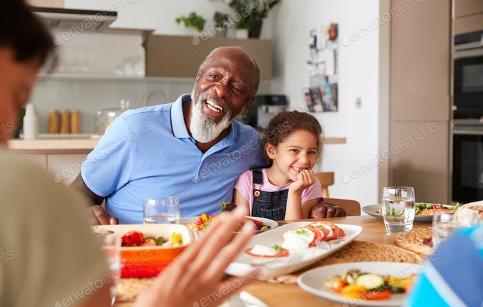 Multi-Generation Mixed Race Family Eating Meal Around Table At Home Together