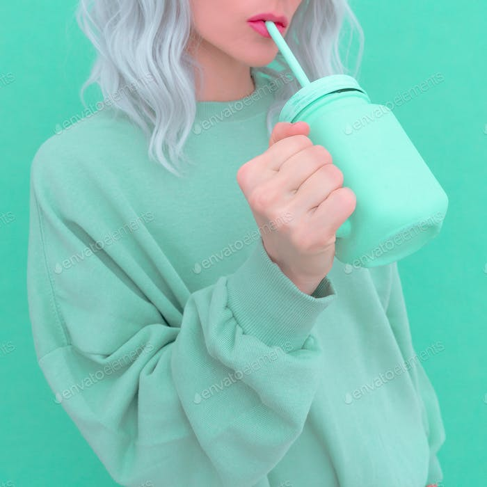 Aesthetic blonde girl drink fresh Smoothie. Minimal monochrome  design. Aqua menthe trend