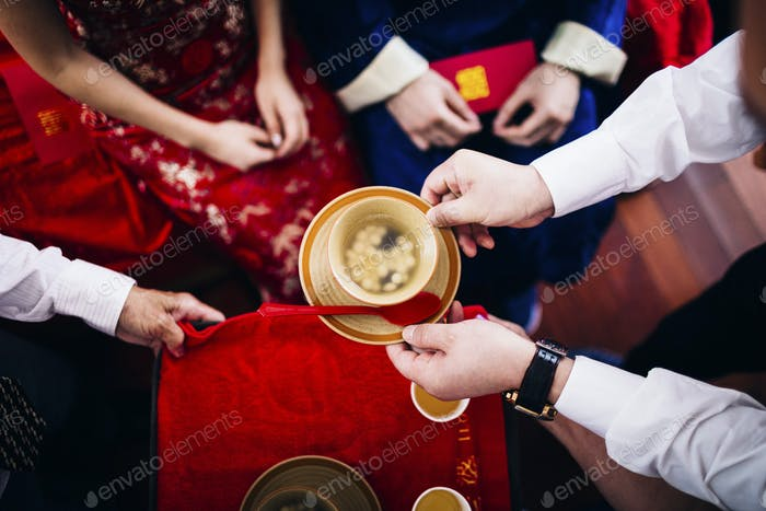High angle close up of a ritual at a Chinese wedding ceremony, people passing a bowl of soup.