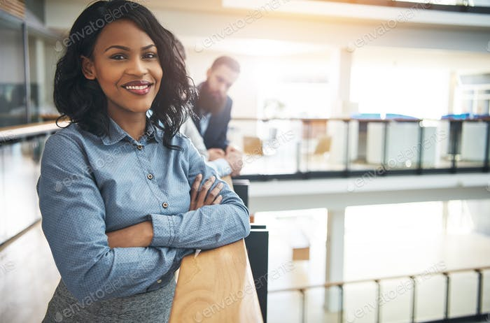 Smiling young businesswoman standing in the hallway of an office