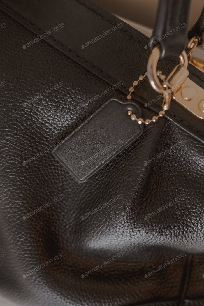 Black tag on genuine pebble leather bag with gold furniture