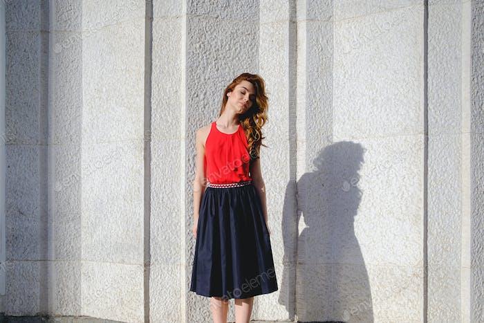 Beautiful girl posing on an urban wall