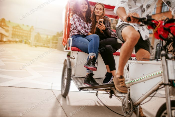 Junge Frauen sitzen auf Dreirad und posieren für selfie