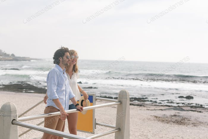 Side view of young Caucasian couple relaxing on the promenade at the seaside. They are smiling