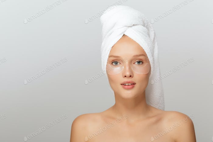 Portrait of pretty lady with white towel on head without makeup