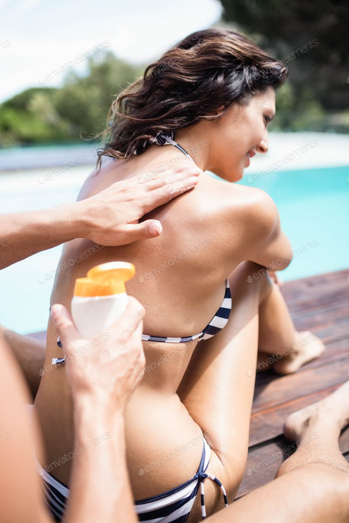 Man applying sunscreen on back of her womannear pool on a sunny day