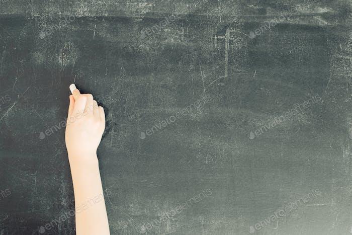 child's hand with chalk on black chalkboard