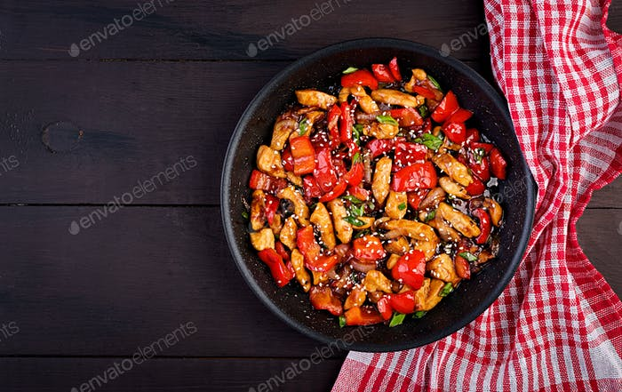 Stir fry chicken, sweet peppers and green onion. Top view. Asian cuisine