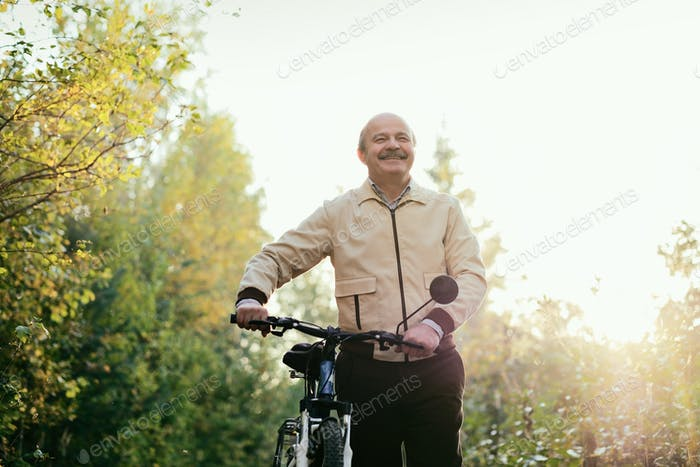 Senior man go for a walk with bike in countryside