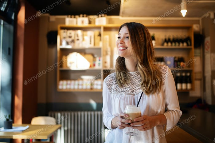 Happy beautiful young woman resting in coffee shop