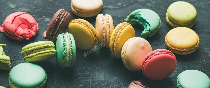Colorful French macaroons over black background, wide composition