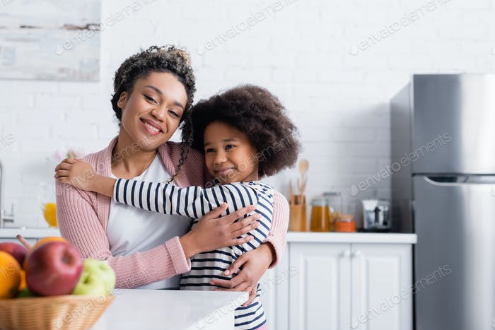 happy african american mom and child smiling at camera near fruits on blurred foreground