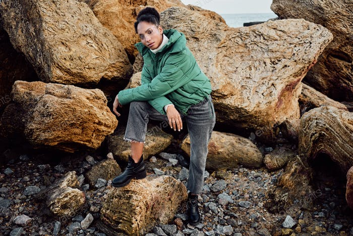 African American girl in stylish down jacket confidently looking in camera on rocks by the sea