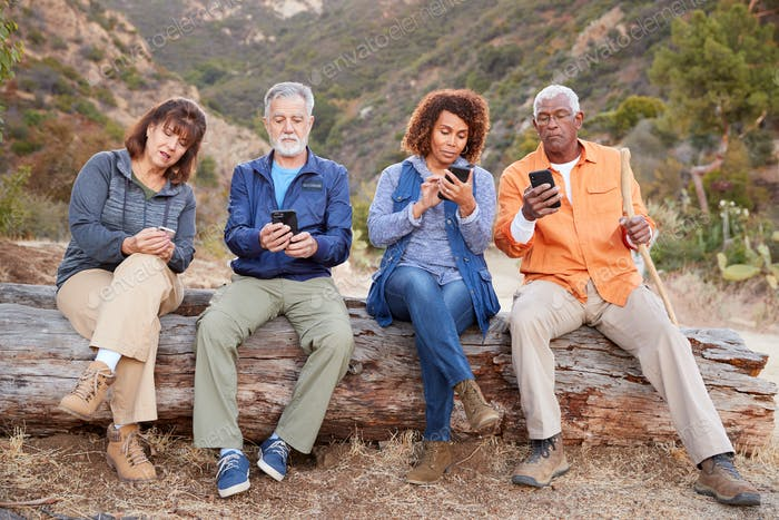 Group Of Senior Friends On Hike In Countryside Checking Mobiles Phones For Fear Of Missing Out