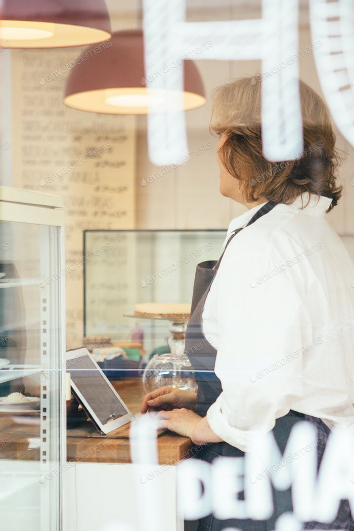 Side view of adult woman at cafe counter