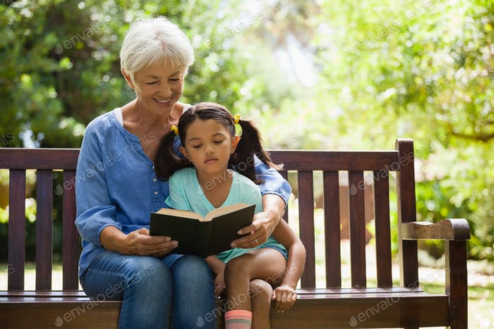Grandmother reading novel to granddaughter sitting on wooden bench