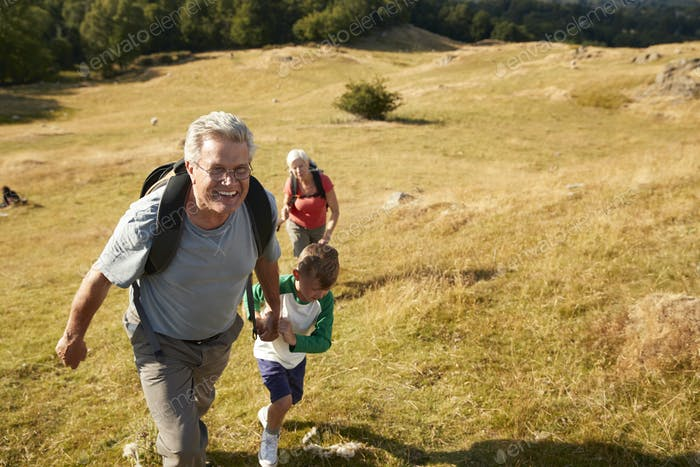 Grandparents With Grandchildren Climbing Hill On Hike Through Countryside