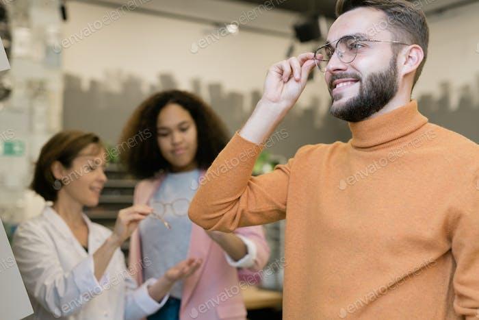 Glückliche Kerl versucht auf Paar Brillen auf Hintergrund der Berater und Client