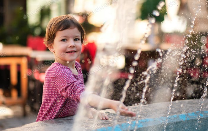Small girl standing by water fountain outdoors in town