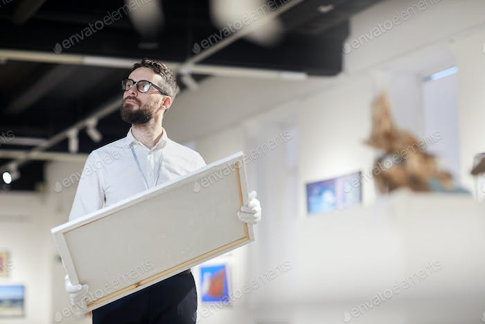 Bearded Worker Holding Painting in Art Gallery
