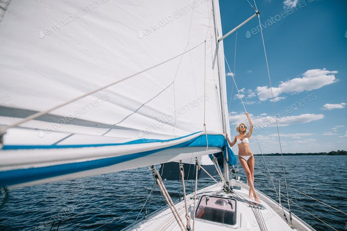 distant view of attractive young woman in swimwear standing on yacht