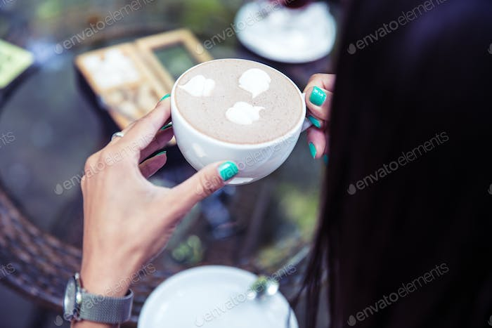 Woman holding cup with coffee