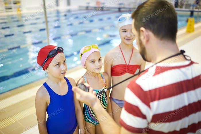 Group of girls listening to swim trainer