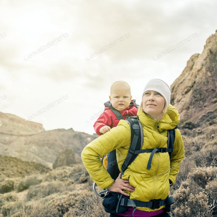 Superhero mother with little boy travelling in backpack