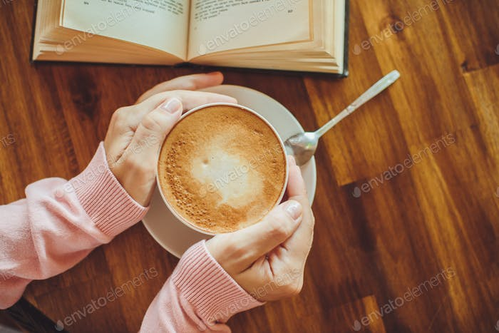 Women's hands holding hot coffee