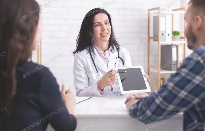 Doctor showing test results on digital tablet to married patients
