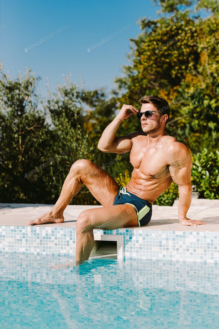 Handsome muscular man relaxing in swimming pool outdoors and sunbathe