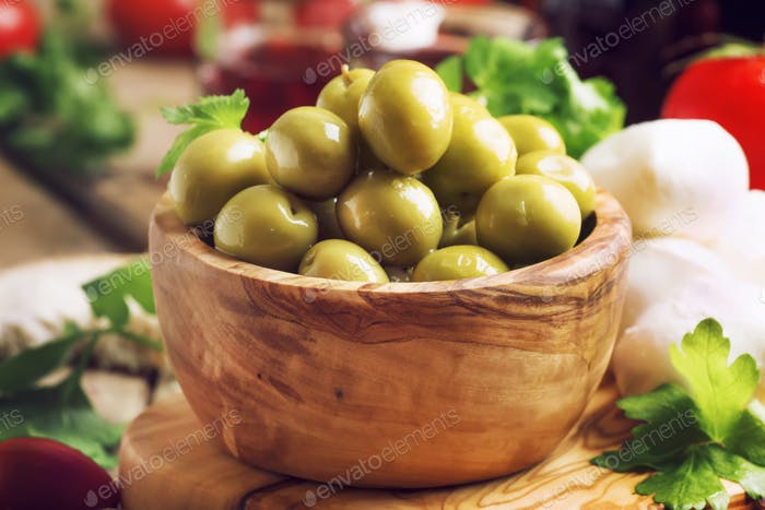 Salted Spanish green olives in wooden bowl and appetizers